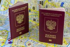 reis concept Twee Russische paspoorten op de achtergrond van een document kaart van de stad royalty-vrije stock afbeeldingen