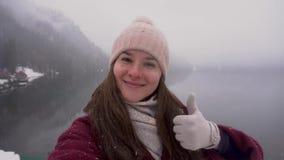 reis concept Vrouw die duim tonen bij Ritsa-meer in Abchazië in de winter stock video