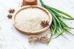 Reis in der hölzernen Platte und im Anis auf weißem hölzernem Hintergrund Reis und Gewürze im ökologischen Behälter stellen Sie f Lizenzfreie Stockfotografie