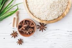 Reis in der hölzernen Platte und im Anis auf weißem hölzernem Hintergrund Reis und Gewürze im ökologischen Behälter stellen Sie f Stockfoto