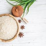 Reis in der hölzernen Platte und im Anis auf weißem hölzernem Hintergrund Reis und Gewürze im ökologischen Behälter stellen Sie f Stockfotos