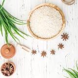 Reis in der hölzernen Platte und im Anis auf weißem hölzernem Hintergrund Reis und Gewürze im ökologischen Behälter stellen Sie f Stockfotografie