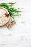 Reis in der hölzernen Platte und im Anis auf weißem hölzernem Hintergrund Reis und Gewürze im ökologischen Behälter stellen Sie f Stockbilder