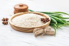 Reis in der hölzernen Platte und im Anis auf weißem hölzernem Hintergrund Reis und Gewürze im ökologischen Behälter stellen Sie f Lizenzfreie Stockbilder
