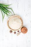 Reis in der hölzernen Platte und im Anis auf weißem hölzernem Hintergrund Reis und Gewürze im ökologischen Behälter stellen Sie f Stockbild