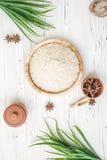 Reis in der hölzernen Platte und im Anis auf weißem hölzernem Hintergrund Reis und Gewürze im ökologischen Behälter stellen Sie f Lizenzfreies Stockbild