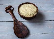 Reis in der Platte und im hölzernen Löffel Lizenzfreie Stockbilder