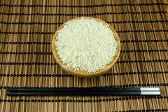 Reis in der Schüssel mit Essstäbchen auf traditioneller asiatischer Platten-Matte Lizenzfreies Stockfoto
