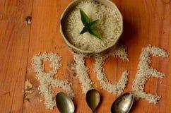 Reis in der Weinleseschüssel mit drei Weinleseteelöffeln auf hölzernem Hintergrund, reis, arroz, riso, riz, риÑ- Stockfoto