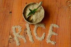 Reis in der Weinleseschüssel mit Weinleseteelöffel auf hölzernem Hintergrund, reis, arroz, riso, riz, риÑ- Lizenzfreie Stockfotos