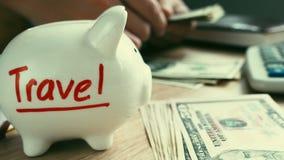 Reis die op een spaarvarken en handen geld houden Besparingen voor vakantie stock footage