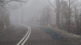 Reis door auto op een sneeuwweg Moeilijke reisvoorwaarden op de lokale weg stock video