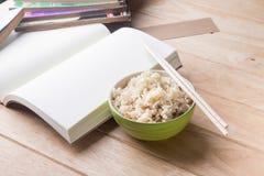 Reis eine Schüssel mit Essstäbchen und Reste eines Buches auf einem hölzernen Schreibtisch. Lizenzfreie Stockfotos