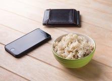 Reis eine Schüssel mit Essstäbchen und Reste eines Buches auf einem hölzernen Schreibtisch. Stockfoto