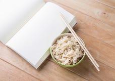 Reis eine Schüssel mit Essstäbchen und Reste eines Buches auf einem hölzernen Schreibtisch. Lizenzfreie Stockbilder