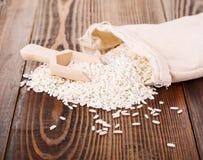 Reis in einem Leinensack auf Holzoberfläche Stockfotos