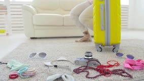 Reis en Vakantieconcept De gelukkige jonge vrouw pakt kleurrijke de zomerkleren in bagagekoffer voor in nieuw stock video
