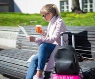 Reis en vakantieconcept - de jonge zitting van de vrouwentoerist in park met kaart en koffer stock fotografie