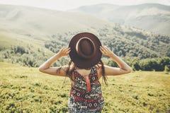 reis en zwerflustconcept de holdingshoed van het reizigers hipster meisje royalty-vrije stock afbeeldingen