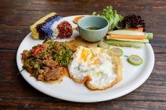 Reis mit angebratenem Schweinefleisch und Basilikum Stockfoto