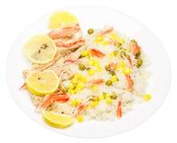 Reis mit Fischen, Garnele, Erbsen, Mais und Zitrone auf einer weißen Platte I lizenzfreies stockbild
