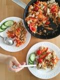 Reis mit Gemüse und Huhn in einer Bratpfanne und auf Platten für Abendessen Stockbild