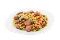 Reis mit Gemüse und Würsten Stockbild