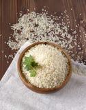 Reis mit Kräutern in einer hölzernen Platte auf Leinenserviette Stockbilder