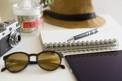 Reis planningsconcept op lijst Reizigers` s toebehoren en punten met notitieboekje en de kruik van de geldbesparing, zonnebril en Stock Afbeelding