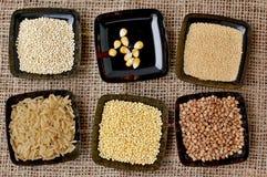 Reis, Quinoa, Mais, Hirse, Buchweizen, Amarant im Schwarzblech auf dem Juteleinwandstoff Stockfotografie