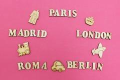 Reis rond de wereld, de namen van steden: 'Parijs, Londen, Madrid, Berlijn, Rome 'op een roze achtergrond Houten cijfers van a stock afbeeldingen