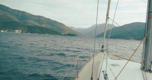 Reis rond Europa Montenegro en Albanië Witte bootritten over Baai van Kotor in een zonnige dag stock footage
