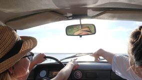 Reis samen op auto, backlight, meisje twee in auto in zonlicht wordt gesproken, wijfjes die in auto bij achtergrond spreken die stock footage