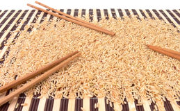 Reis und Ess-Stäbchen auf Bambusteppich Stockfotos