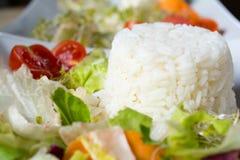 Reis und Salat auf weißer Platte Lizenzfreies Stockfoto