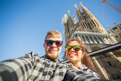 Reis, vakantie en mensenconcept - Gelukkig paar die selfie foto voor Sagrada Familia in Barcelona nemen stock afbeeldingen