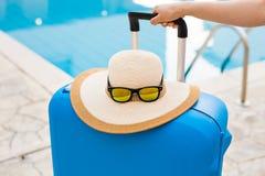 Reis, vakantie en vakantieconcept - Blauwe koffer, hoed en zonnebril dichtbij zwembad stock afbeelding