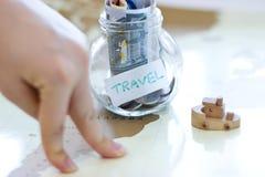 Reisbegroting - de besparingen van het vakantiegeld in een glaskruik op wereld m Stock Afbeelding
