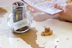 Reisbegroting - de besparingen van het vakantiegeld in een glaskruik op wereld m Stock Foto's