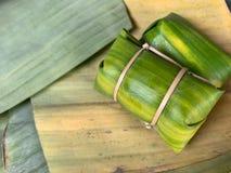 Reisbrei, Bananen mit klebrigem Reis auf grünen Bananenblättern, die mit einem Hammer oder einem Khao Tom Mat banden, thailändisc lizenzfreies stockfoto