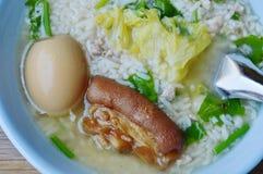 Reisbrei, der Bein des braunen Eies und des Schweinefleisch in der Schüssel übersteigt Lizenzfreie Stockbilder