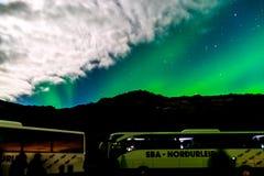 Reisbussen in Aurora Borealis of Noordelijke Lichten in Reykjavik, IJsland royalty-vrije stock foto