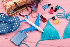 Reisconcept - de manier van de zomervrouwen met zak, blauw zwempak, zonnebril, wipschakelaars, nagellak, notastootkussen en weini stock foto's