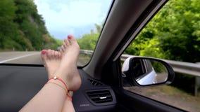 Reisconcept met gemak - vrouwelijke benen op autopaneel Windschermvenster en vrouwelijke benen met pedicure en stock videobeelden