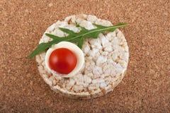 Reiscracker mit Tomate auf einer Korkentabelle Lizenzfreies Stockfoto