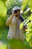 Reise auf Safarireise: Porträt des Touristen oder des Erforschungswissenschaftlermannes im Tropenhelm, der Spaß hat, das Schauen  Stockbilder