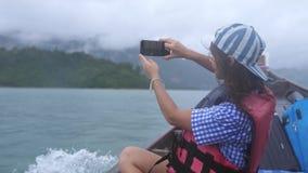 Reise der jungen Frau auf dem sich schnell bewegenden touristischen hölzernen Boot mit Koffer macht Foto mit Handy in bewölktem stock video footage