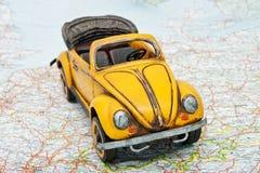 Reise durch Auto. Ein Spielzeugauto auf der Karte Stockfoto