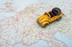 Reise durch Auto. Ein Spielzeugauto auf Europa-Karte Lizenzfreie Stockfotografie