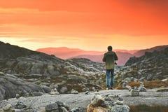 Reise-Mann, der Sonnenuntergangberge genießend geht stockfotos
